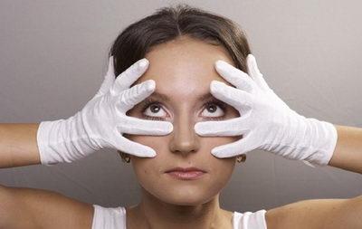 Девушка в белых перчатках подтягивает веки