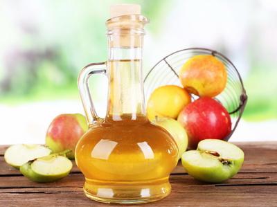 Apple cider vinegar in glass bottle and ripe fresh apples, on wo